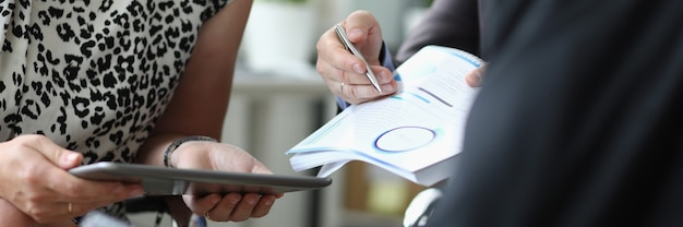 Woman holds tablet in hands next to men with ballpoint pen and documents in hands in office closeup. signing business contracts concept.