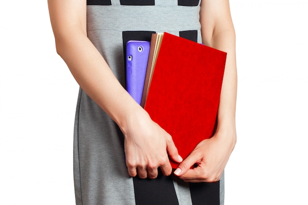 Woman holds tablet and notebook on white background.