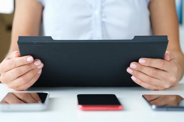 여자는 테이블 3개의 스마트폰에 태블릿을 들고 멀티태스킹 현대 기술 개념을 갖추고 있습니다.