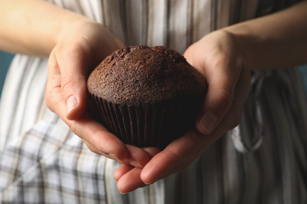 Woman holds tasty chocolate muffin, close up