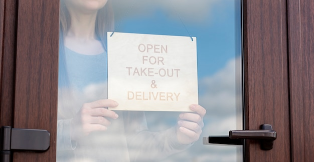Женщина держит деревянный знак с текстом: открыт на вынос и доставку