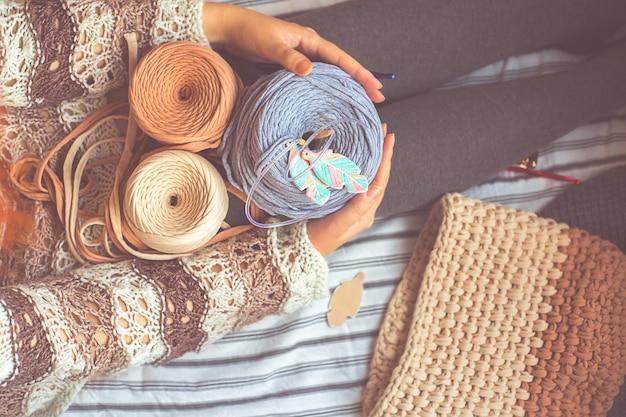 女性は、青い編みのフックで3つのリールスレッドを保持しています