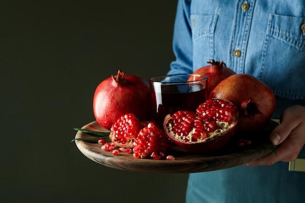 여자는 석류 주스와 재료 트레이를 보유하고, 클로즈업