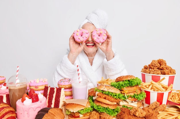 Woman holds two delicious glazed doughnuts on eyes smiles gladfully surrounded by junk food consumes much calories per day wears bathrobe