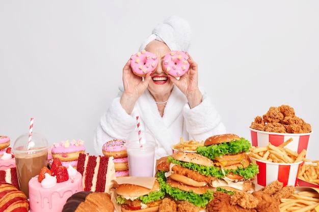 La donna tiene due deliziose ciambelle glassate sugli occhi sorride felice circondata da cibo spazzatura consuma molte calorie al giorno indossa accappatoio