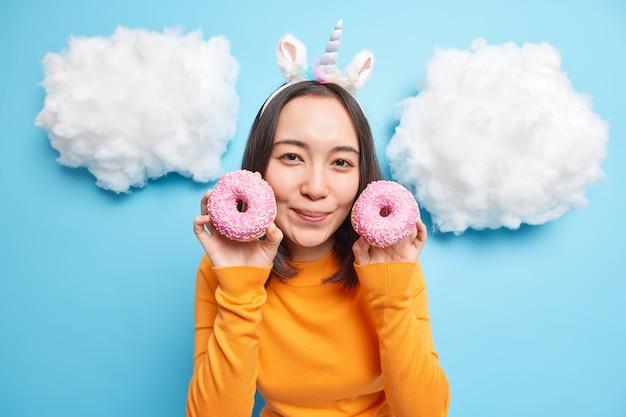 여자는 부드럽게 오렌지 점퍼를 입고 얼굴 미소 근처에 두 개의 유약을 바른 도넛을 보유하고 파란색에 고립 된 맛있는 달콤한 디저트를 먹고 즐긴다