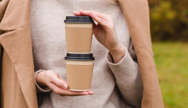 女性は2つの紙のコーヒーカップを持っています