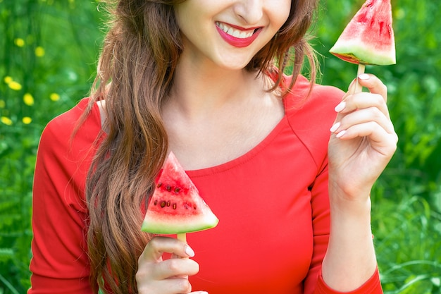 Woman holds two pieces of watermelon.