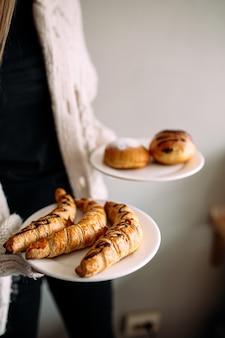 女性は甘いベーグルとパンで2つのプレートを保持します