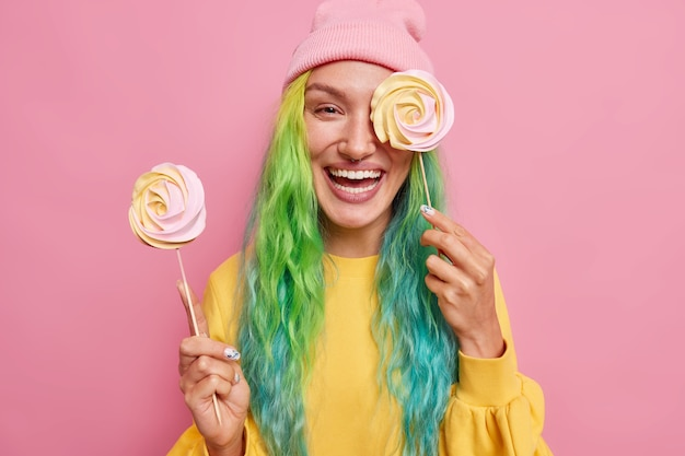 Woman holds two round candies on sticks cons eye with delicious caramel lollipop has colorful hair wears yellow jumper and hat isolated on pink