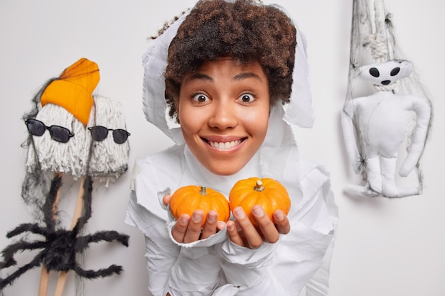 Woman holds two small pumpkins prepares decorations for halloween holiday smiles happily poses on white with creepy creatures around