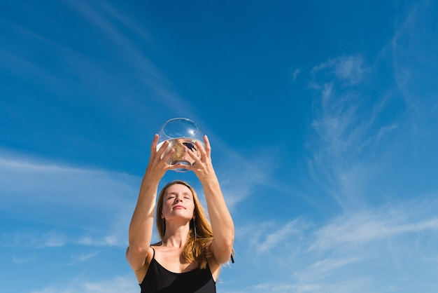 Woman holds up round aquarium with black fish