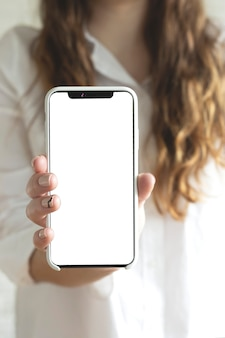 Woman holds and uses smartphone with a blank white screen