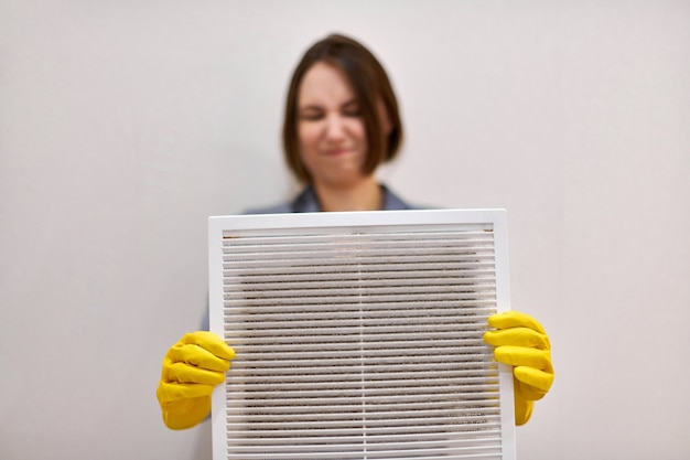 Woman holds ventilation grill with dust filter to clean it. dirty and dusty white plastic, harmful for health. cleaning lady with disguised expression, blurred, in protective rubber gloves and uniform