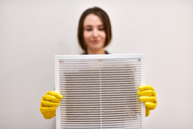 Woman holds ventilation grill with dust filter to clean it. extremely dirty and dusty white plastic, harmful for health
