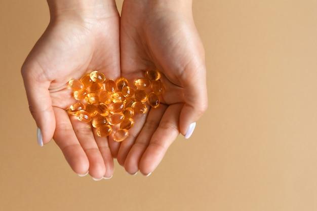 女性は手のひらにビタミンオメガ3カプセルまたは錠剤を持っています。健康的な食事とダイエットの概念。