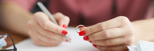 여자는 결혼 반지를 들고 진술서를 씁니다.