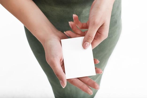 Женщина держит в руке белую карточку