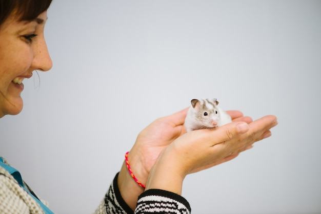 Woman holds white furry little mouse.