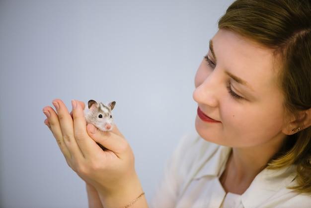 Женщина держит белый пушистый мышонок.