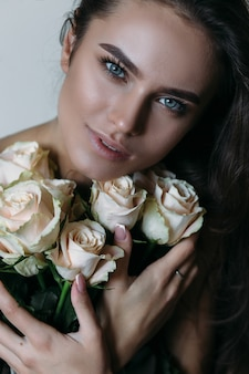Woman holds white roses before her chest