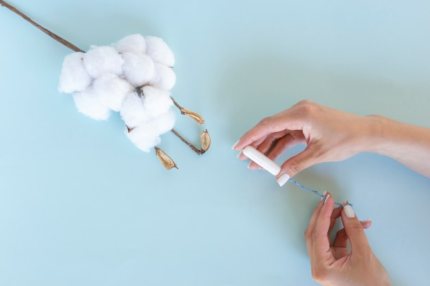 A woman holds a white sanitary tampon in her hands. menstruation days. hygiene and body care concept