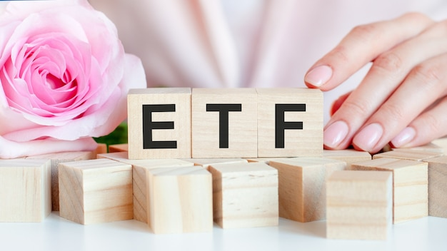 A woman holds a wooden cube with the text of etf in her hand.