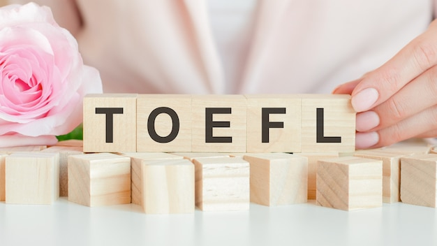 Woman holds a wooden cube with the text of toefl in her hand. on the wooden cubes there is a living rose flower. pink background, front view. business, economic, education concept