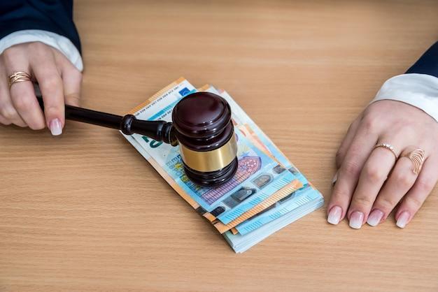 女性はユーロで紙幣の上に木製のハンマーを保持します