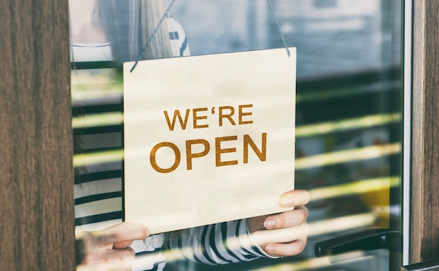Woman holds the wooden sign with text: we're open