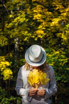 Женщина держит в руке желтые листья