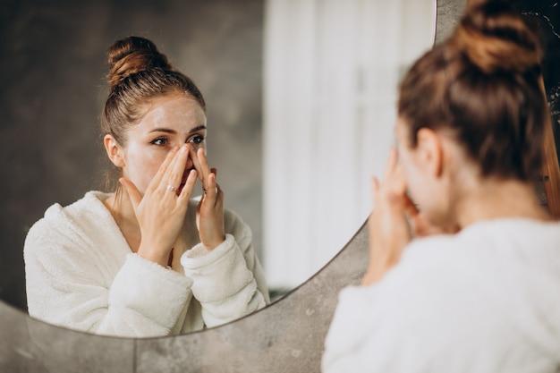 Donna a casa che applica la maschera crema