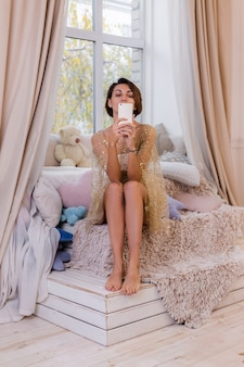 Woman at home in bedroom wearing evening christmas dress, taking photo selfie