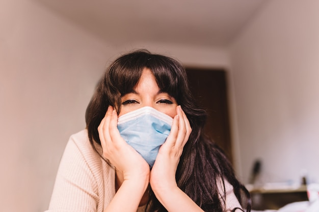 Woman at home in breathing medical respiratory mask on her face smiling hopefully. pandemic coronavirus, virus covid-19. quarantine, prevent infection concept.