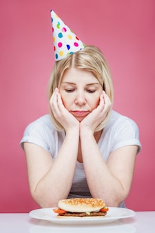 A woman in home clothes and a festive cap sits sad in front of a hamburger on a plate. lonely birthday in isolation period on the background of coronavirus. pink background. vertical.