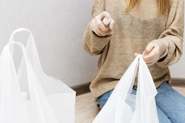Woman in home clothes and rubber gloves on her hands disinfects surface of plastic bags with products from store