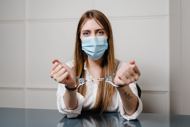 Woman at home behind desk wearing mask and handcuffs. safety and security concept