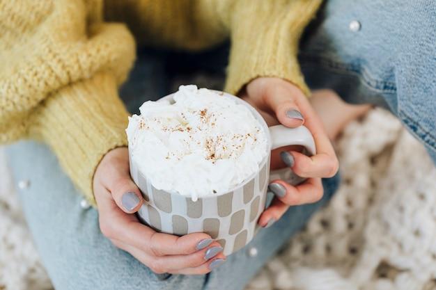 Donna a casa a bere cioccolata calda con panna montata