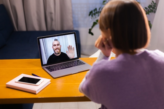 Woman at home face time video call her friends husband boyfriend, chatting online from laptop