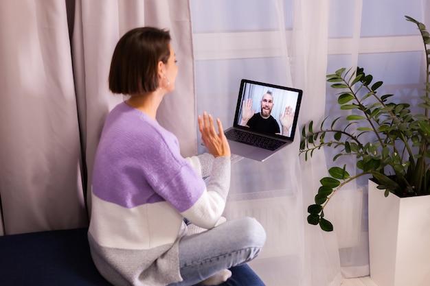 La donna a casa faccia video chiama i suoi amici marito fidanzato, chattando online dal laptop