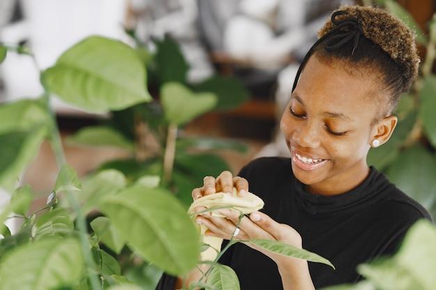 La donna a casa. ragazza con un maglione nero. la donna africana usa lo straccio. persona con vaso di fiori.