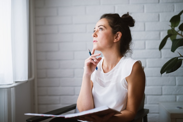 Woman at home holding notebook working business from home.