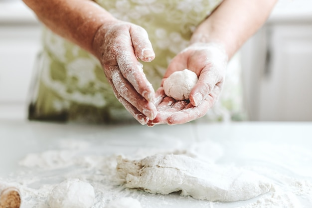Woman at home kneading dough for cooking pasta pizza or bread. home cooking concept. lifestyle