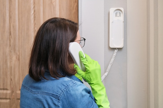 Woman at home near front door talking on intercom, answering the call, holding security phone in hand