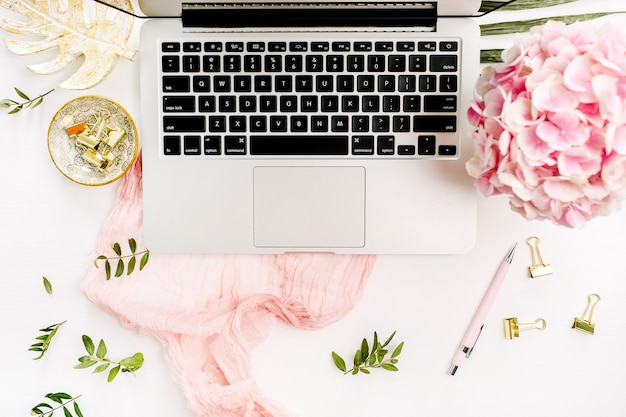 Стол домашнего офиса женщины с компьтер-книжкой, цветками и аксессуарами на белой поверхности. плоская планировка, вид сверху