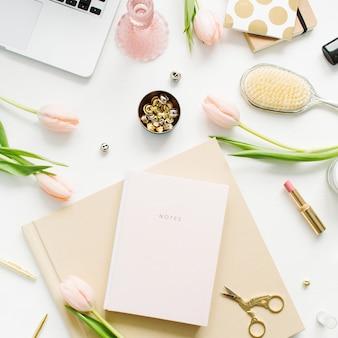 女性のホーム オフィス デスク。ノート パソコン、ピンクのチューリップの花、ノート、アクセサリー、化粧品を備えたワークスペース。フラットレイ、トップビュー