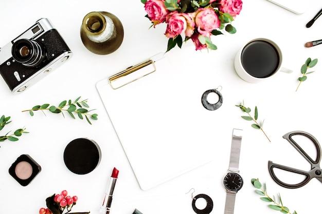 クリップボード、ノート パソコン、バラの花、ユーカリの枝、ファッション アクセサリー、化粧品を備えた女性のホーム オフィスのワークスペース。フラットレイ、トップビューファッションモックアップ