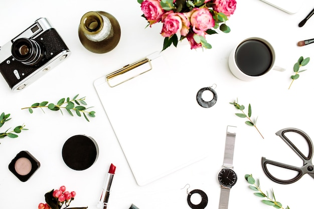 Woman home office workspace with clipboard, laptop, rose flowers, eucalyptus branches, fashion accessories and cosmetics. flat lay, top view fashion mockup