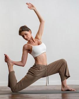 La donna a casa a praticare yoga sulla stuoia