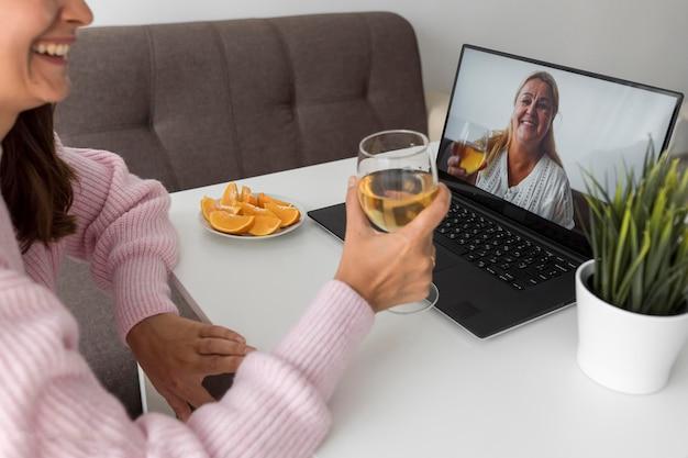 Donna a casa in quarantena a bere un drink con un amico sul laptop